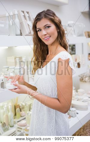 Portrait of smiling woman testing moisturizer and looking at camera at a beauty salon