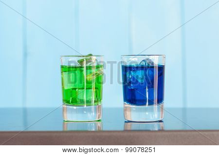 Blue, green shorts drink or liqueur with ice cube on light background. Cocktail card