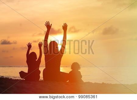 happy mother with two kids having fun at sunset
