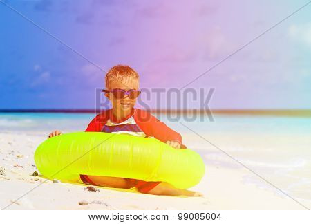 little boy playing with life ring at tropical beach