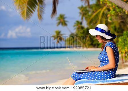young woman with laptop on tropical beach