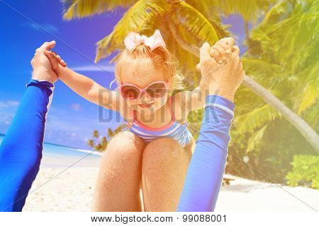 father and little daughter play at beach