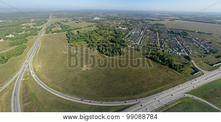 Aerial city view with crossroads, roads, houses, buildings, parks, parking lots