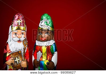 Close up of Sinterklaas and Black Pete . Saint  Nicholas chocolate figure of  Dutch character of Santa Claus on red background.