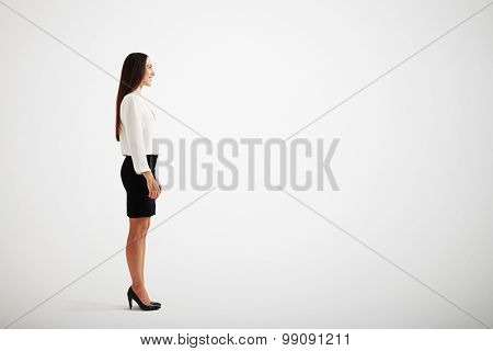 sideview of smiley businesswoman over light grey background
