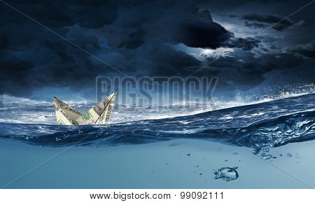 Ship made of dollar banknote sinking in water