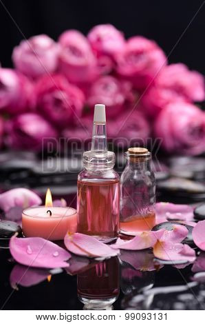 Branch pink rose with candle and oil on wet stones