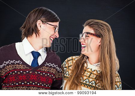 Happy geeky hipster couple looking at each other against blackboard