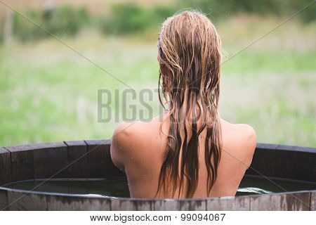 Woman sitting on tub, outdoor