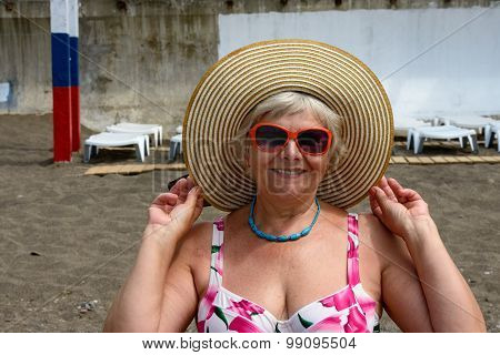 Aged Woman In Straw Hat And Sunglasses On Beach Background.