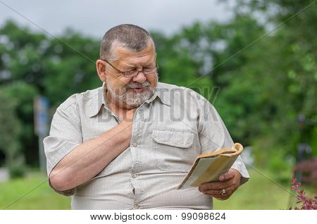Portrait of senior man reading an interesting book