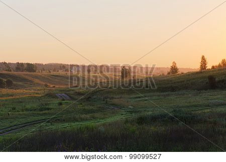 Green Hills With Small Distant Trees In Early Summer Sunrise