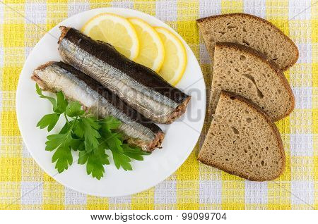 Canned Fish, Lemon, Parsley And Pieces Of Bread On Tablecloth