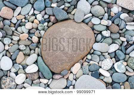Bacground made of pebbles on the beach with one big pebble in the centre