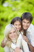 picture of happy family  - Attractive happy family with a child outdoors - JPG