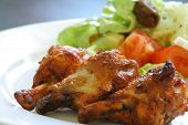 foto of chicken wings  - grilled chicken on a white plate with vegetables on the background - JPG