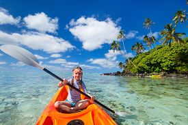 foto of kayak  - Little girl enjoying paddling in colorful orange kayak at tropical ocean water during summer vacation - JPG