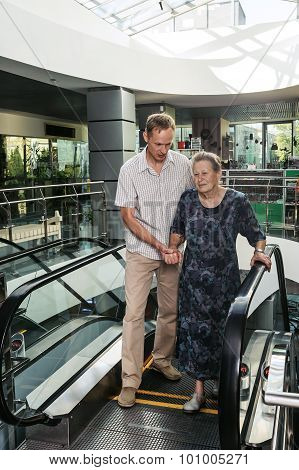 Man Helps The Old Woman Get Off The Escalator