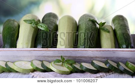 Fresh zucchini with squash and basil on bright background