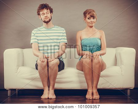 Shy Woman And Man Sitting Close To Each Other On Couch.