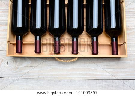 Wine crate with six bottles without labels. Horizontal format with copy space, on a white wood table shot from a high angle.