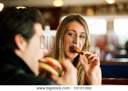 Paar im Restaurant essen Fast food