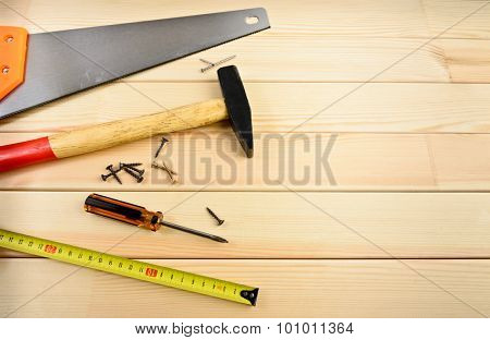 Saw, screw, tape measure and hammer on wood