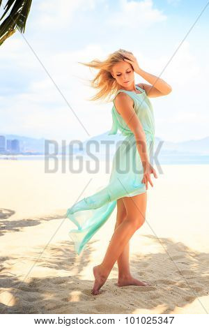 Blonde Girl In Transparent Frock In Palm Shadow On Beach