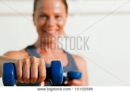 Mujer con pesas en el gimnasio