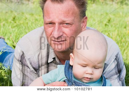 Father And Son Lying On The Grass