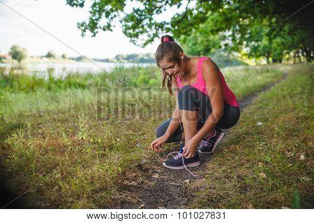 woman girl running around playing sports outdoors tying shoelace