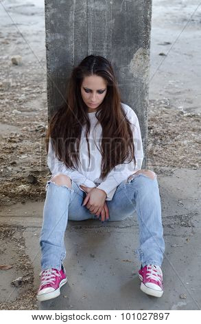 Depressed young girl sitting on the concrete floor of abandoned building
