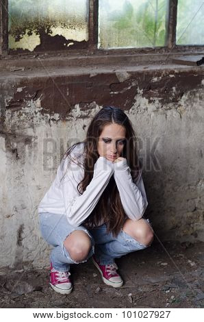 Portrait Of The Depressed Young Girl Leaning Against Ruined Wall In Abandoned Building