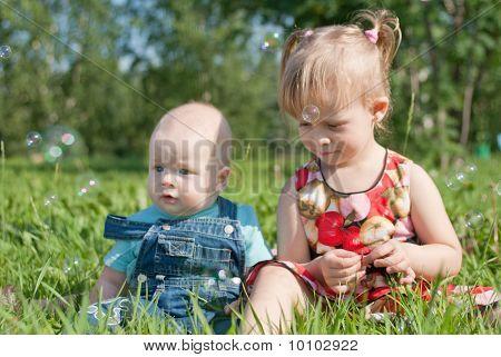Dos niños sentados sobre la hierba