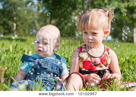 A Boy And Girl Sitting On The Grass