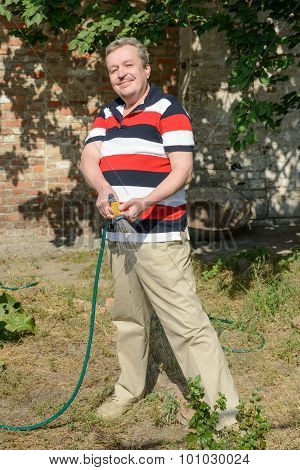 Mature Man Is Watering Garden Plot Using Garden Spray Gun.
