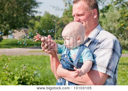 Dad And Son Look At The Bubbles