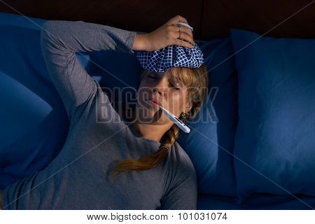 Girl With Fever Holds Thermometer In Mouth At Night