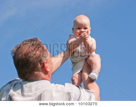 Vater emporgehoben ihr Baby, freut sich das Kind