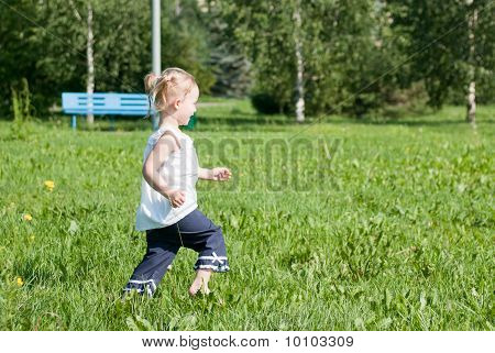 Girl Runs Around The Green Grass In The Park