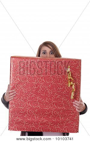 Young Woman Hiding Behind A Big Chrismas Present, Making Big Eyes