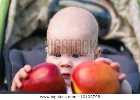 Niño pequeño con ambas manos dos manzanas