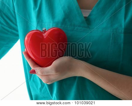 Young woman doctor holding a red heart, in office