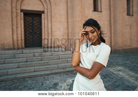 smiling indian lady in white dress against ancient building