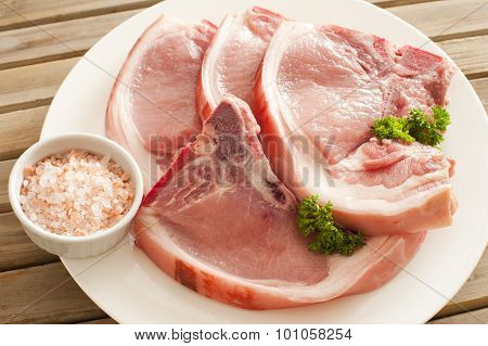 Fresh Pork Chops On Plate With Rock Salt