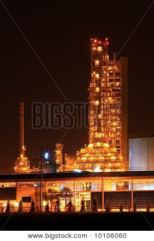 scenic of petrochemical oil refinery plant shines at night vertical closeup