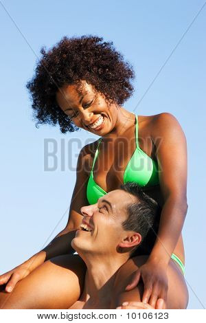 Summer bikini girl sitting on shoulders of man