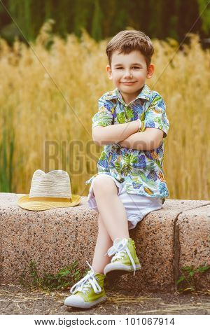 Smiling young fashion boy with hat posing at summer park