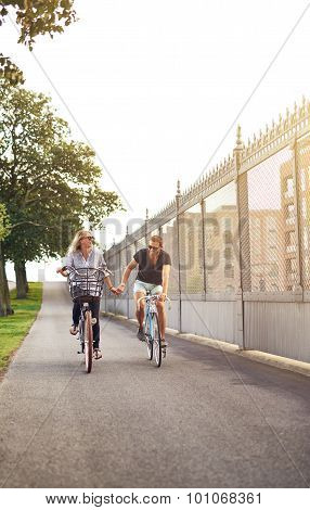 Young Couple Cycling Down A Cycle Lane