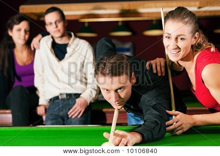 Friends playing billiards together
